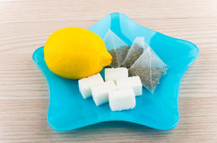 Lemon, sugar and tea bags in blue plate on table Stock Photography