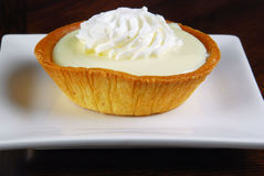 Lemon Tart. Garnished with whipped cream on a white plate Royalty Free Stock Photo