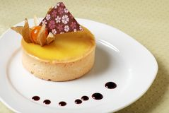 Lemon tart decorated and drops of orange sauce Stock Photo