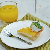 Lemon tart dessert with orange juice drink refreshment. Lemon tart dessert on white plate with orange juice drink refreshment Stock Photography