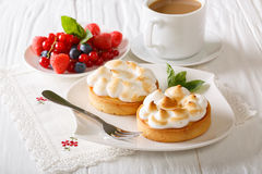 Lemon tart with meringue and berry mix, coffee  close-up. horizo Stock Image