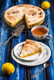 Lemon tart. With meringue topping on a wooden blue table board royalty free stock photo