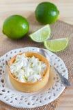 Lemon tart pie on white plate spoone on sackcloth with fresh lim Stock Photography