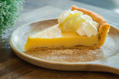 Lemon tart on wooden plate Royalty Free Stock Photography