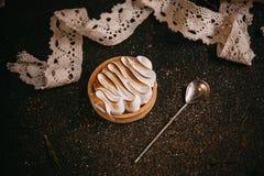 Lemon tartlet with meringue n the stone dark table Stock Photo