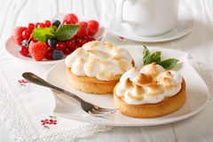 Lemon tartlets with meringue, berries and coffee close-up. horiz Royalty Free Stock Photo