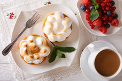 Lemon tartlets with meringue, berries and coffee close-up. horiz Stock Photos