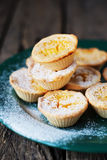 Lemon Tartlets with Powdered sugar on a green plate, wooden back. Ground Stock Photography