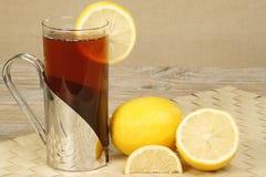 Lemon tea. Glass mug of refreshing hot lemon tea on a wooden table Royalty Free Stock Photography