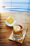 Lemon tea. A cup of black tea with lemon on a table Royalty Free Stock Photo