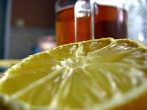 Lemon and tea. Lemon on the foreground and a glass of the tea beyond. Picture made in the village\'s house Stock Photography