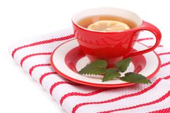 Lemon tea in a beautiful cup and saucer decorated with mint Royalty Free Stock Image