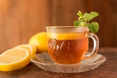Lemon Tea - Cup of lemon slices with tea and mint leaf royalty free stock images