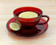 Lemon tea in cup and saucer with rind. A cup of lemon tea with slices floating in the water and a small piece of rind on the saucer atop a wood counter top Stock Images