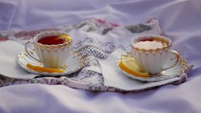 Lemon tea in cups at sunset. Two cups of tea are on skatertet outdoors at sunset 1920x1080. hd stock video footage