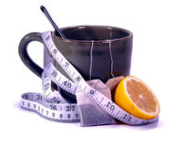 The Lemon Tea Detox. Measuring tape wrapped around a warm mug of lemon tea isolated on white background Royalty Free Stock Photo