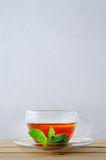 Lemon Tea in Glass Cup with Mint Sprig. Vertical shot of a glass cup containing tea with a slice of lemon on a wooden table.  A sprig of mint leaves rests on the Royalty Free Stock Photography