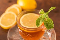 Lemon with tea. Cup of  and mint leaf on a rustic wooden background. Close up, Selective Focus Stock Photo