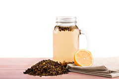 Lemon tea. A mason jar full of hot tea isolated on a white background. Tea leaves and a cut lemon. Organic drinks for breakfast. A sweet black tea and a cut Royalty Free Stock Photo