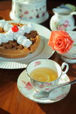 Lemon tea and muffin. Tea cup and teapot with lemon and rose on the table Stock Photos