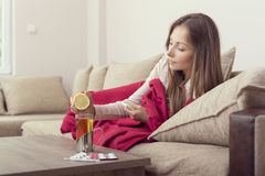 Lemon and tea. Sick woman lying in bed with high fever and a flu, squeezing a lemon juice in her tea Royalty Free Stock Photography