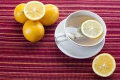 Lemon tea with tea bag on red stripes platemat Royalty Free Stock Images