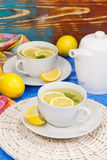 Lemon tea. Two cups with fresh lemon tea with mint on rustic wooden background Royalty Free Stock Photo