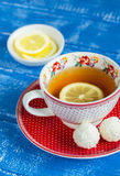 Lemon tea in a vintage Cup and coconut candy Stock Photos