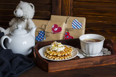 Lemon tea, waffles with ice cream, honey and nuts in a vintage tray,  homemade Valentine's day gifts in kraft paper. On the brown wooden table Royalty Free Stock Photo