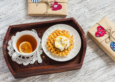 Lemon tea, waffles with ice cream, honey and nuts in a vintage tray, homemade Valentine's day gifts in kraft paper. On a wooden table Royalty Free Stock Images
