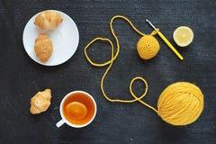 Lemon tea, yellow crocheting and croissants Stock Images