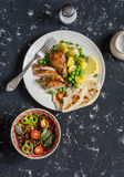Lemon thyme baked chicken, boiled potatoes with green peas, salad with lentils and tomatoes on a dark background. Royalty Free Stock Image