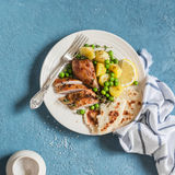 Lemon thyme baked chicken, potatoes and green peas on a white plate on a blue background. Delicious lunch Stock Images