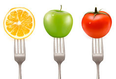 Lemon, tomato and apple on forks Stock Image