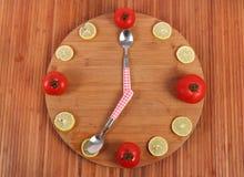 Lemon and tomato clock. Beautiful shot of clock made of tomato and lemon Royalty Free Stock Photography