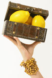 Lemon treasure chest. A treasure chest filed with lemons, held by a gentle and exotic female hand Stock Photo