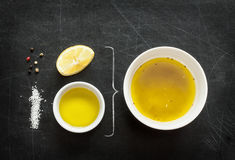 Lemon vinaigrette dressing - recipe ingredients on black chalkboard. Background from above. Lemon, olive oil, salt and pepper. Layout with free text space Stock Photo