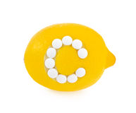 Lemon with vitamin c pills over white background Stock Photos