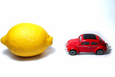 Lemon vs car. A lemon and red car on white background stock photo