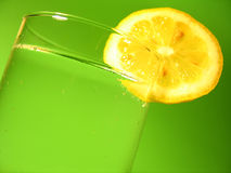Lemon Water. A glass of carbonated water with a lemon slice and vibrant green background Royalty Free Stock Image