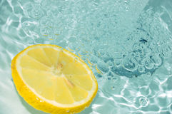 Lemon in water #2. Blue water and fresh lemon royalty free stock image