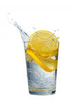 Lemon and water. Glass of fresh water with falling lemons isolated on white Stock Photos