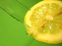 Lemon Water 3. A glass of carbonated water with a lemon slice and vibrant green background. Focus on lemon royalty free stock photos