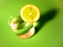 Lemon Water 4. A glass of carbonated water with a lemon slice and vibrant green royalty free stock photo