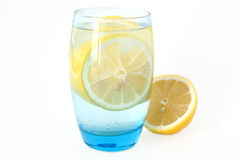 Lemon in water. Lemon in glass with mineral water and ice Royalty Free Stock Photography