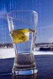 Lemon Water. A partially drunk glass of water with a lemon Stock Image