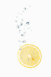 Lemon in water with air bubbles. Lemon falling into water, with air bubbles, in front of white background, union of the three things essential to live which is stock photography