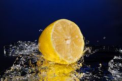 Lemon water with a big splash on blue background mirror stock images