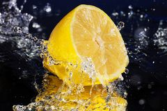 Lemon water with a big splash on blue background royalty free stock photos