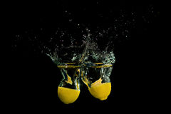 Lemon in water on black background Royalty Free Stock Images